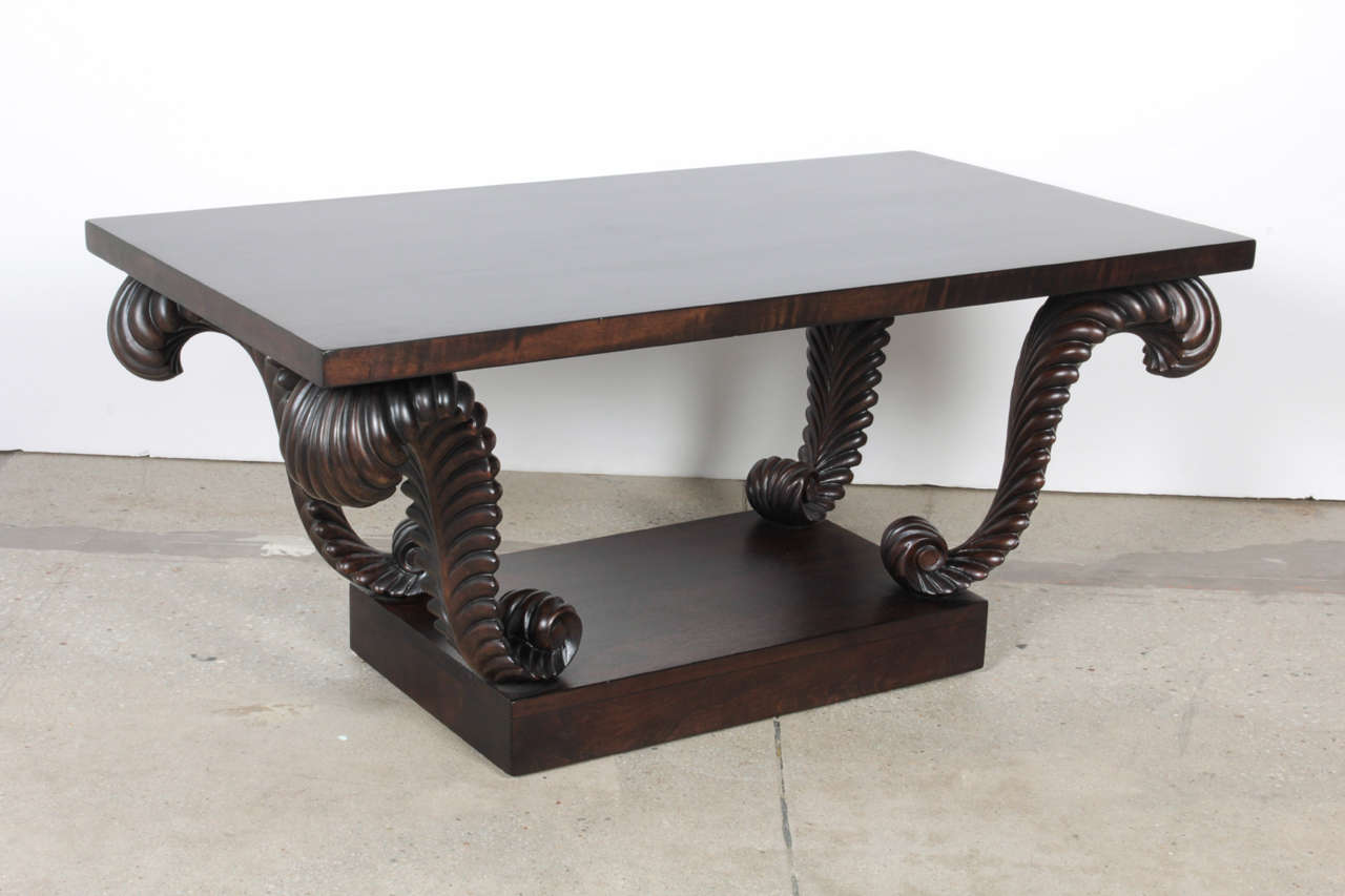 Art Deco influenced Walnut coffee table with carved plume supports by Grosfeld House. Mint restored condition.