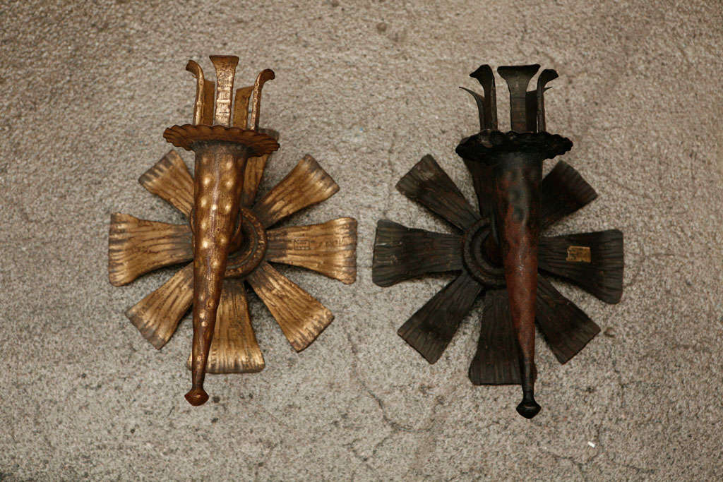 Set of two Spanish hand-forged and hammered wrought iron sconces. We have one in gold antique finish and one in rust iron color finish. They are not wired for electricity, made for candles but could easily be rewired.