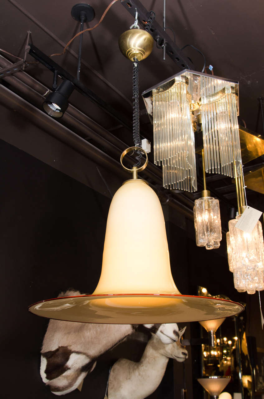 Outstanding mid-century modern large pendant light fixture with stunning elongated bell formation. Handblown Murano glass in hues of parchment with amber glass rim. Features a stylized brass ring fitting with fabric coiled cord.