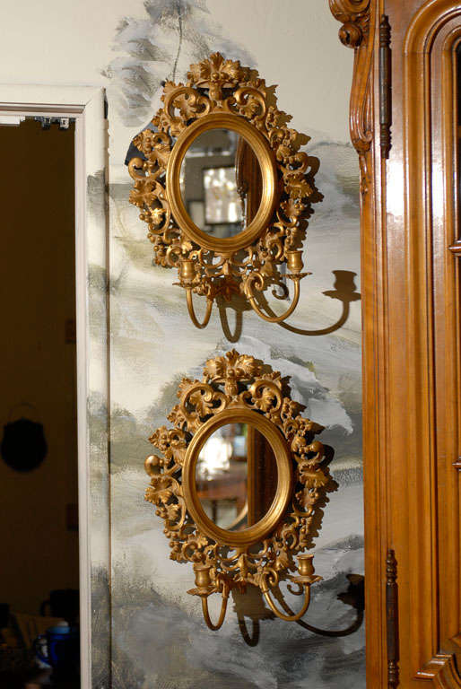 Pair of Italian gilt candle sconces with oval mirrors framed in a beveled frame and surrounded by pierced decorative carving featuring C-scrolls, foliage, and berries. Two candle arms per sconce (not electrified).