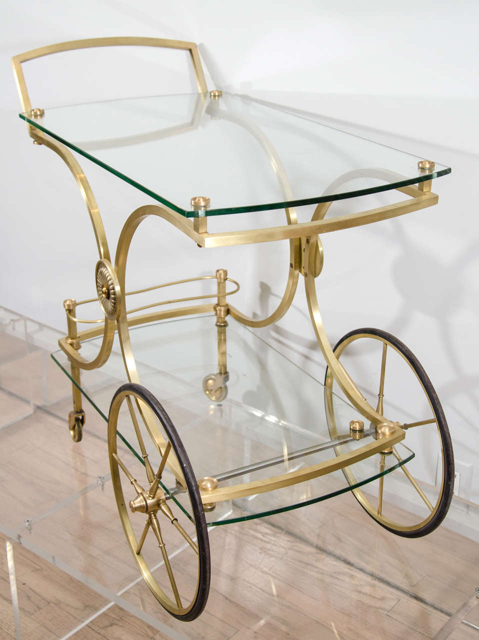Elegant barcart finished in satin gilt brass with elevated glass tops.