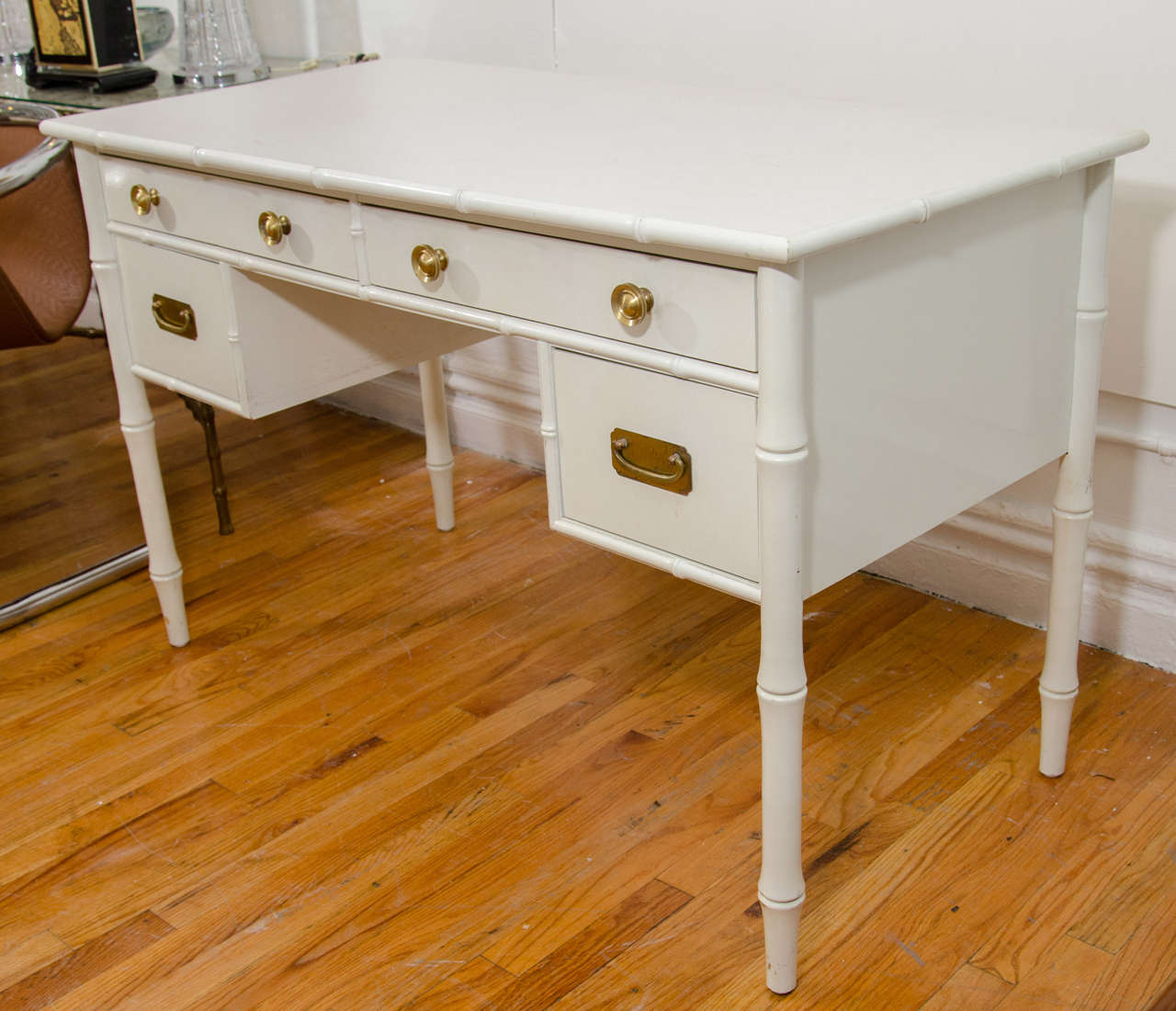 A Hollywood Regency Style Desk With White Paint Over Wood Faux Bamboo Motif And Brass