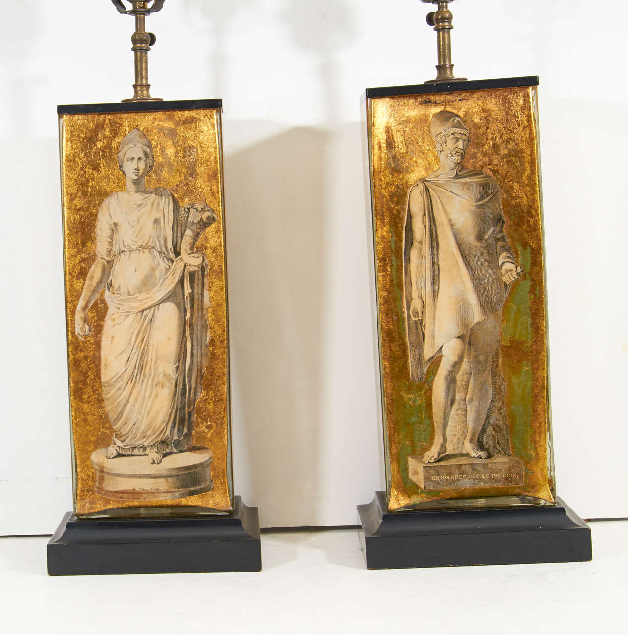 A pair of vintage table lamps attributed to Piero Fornasetti. They have glass bodies with Greco-Roman neoclassical motifs in eglomise and sit on ebonized wood bases.  Reduced from: $5,500