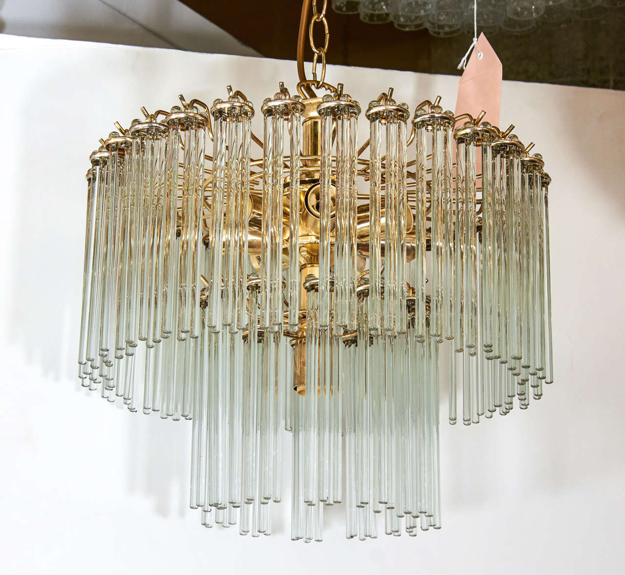 A Vintage Two Tier Chandelier With Thin Glass Rods Suspended From Brass Frame
