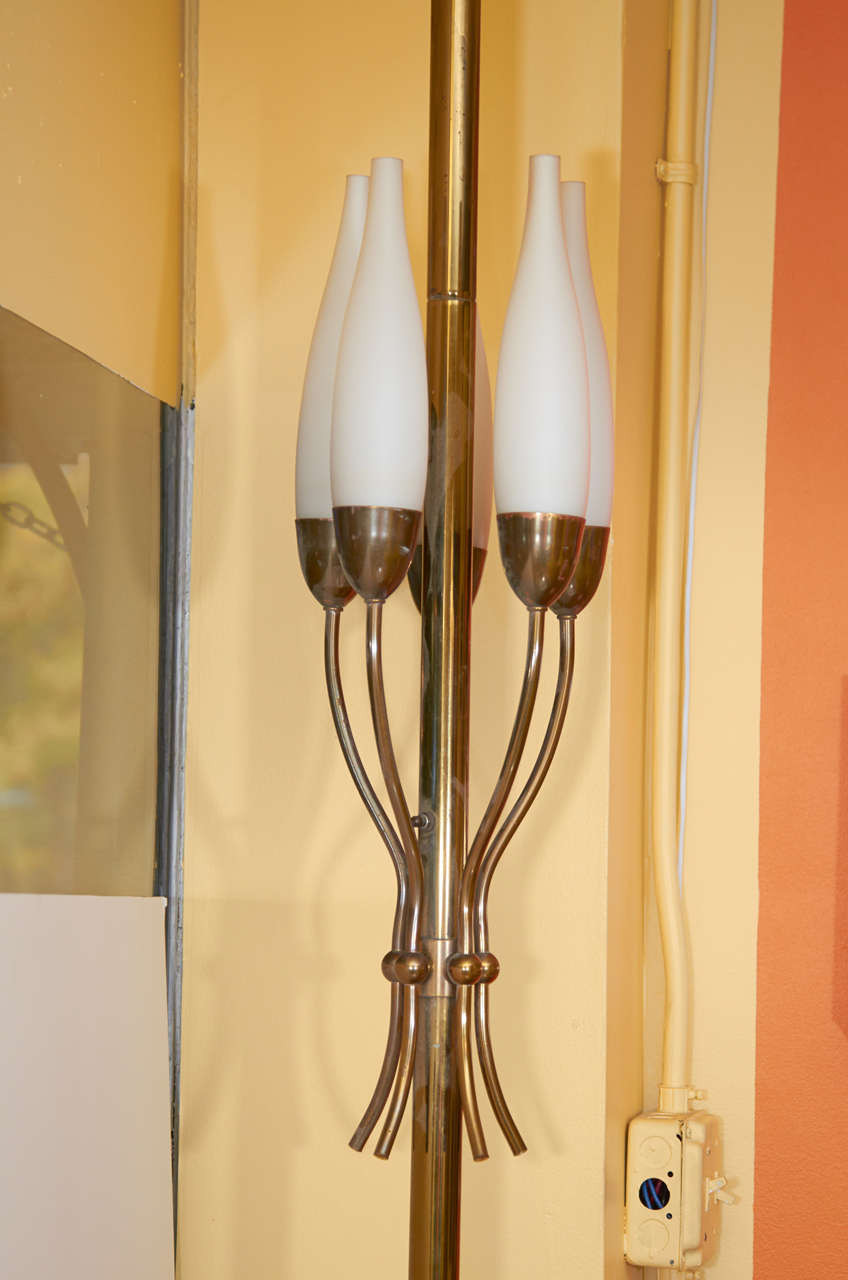 Beautiful lamp by Angelo Lelii for Arredoluce. This brass floor lamp has a gracefully designed cluster of Lelii's signature frosted candle shades. It is a pole lamp with spring loaded mounts to fix the lamp in place between floor and ceiling. Please
