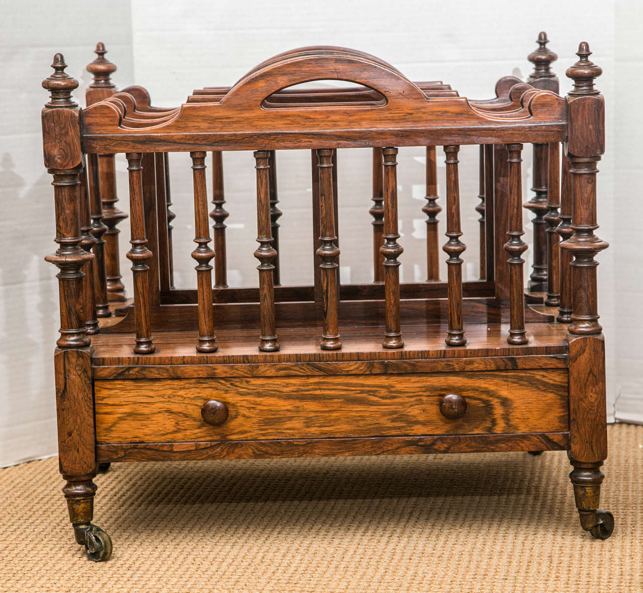 A handsome three-section Canterbury with four pierced handles, turned columns, a lower drawer, and original casters.
