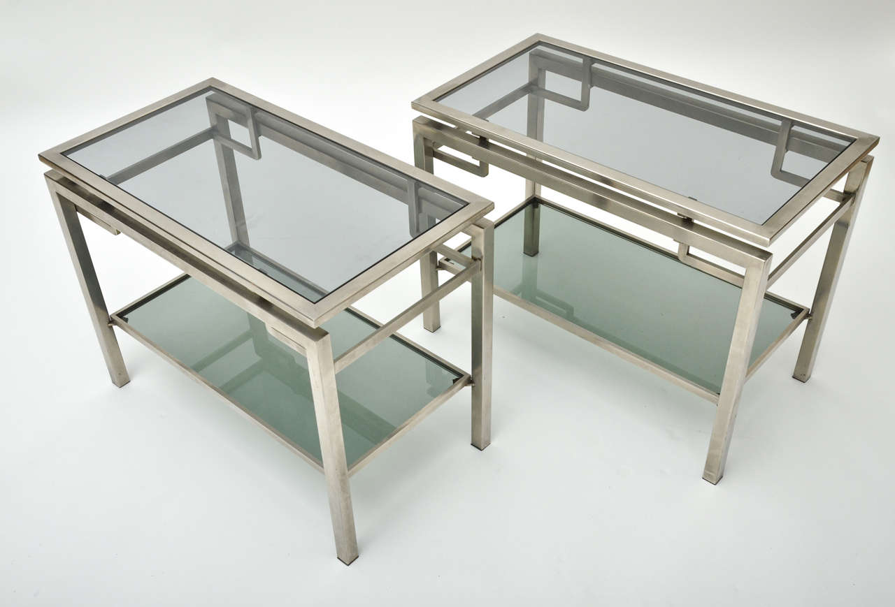 A pair of 1960s French Guy Le Fevre chrome side tables with two tiers in brushed chrome. Matching coffee table available.
