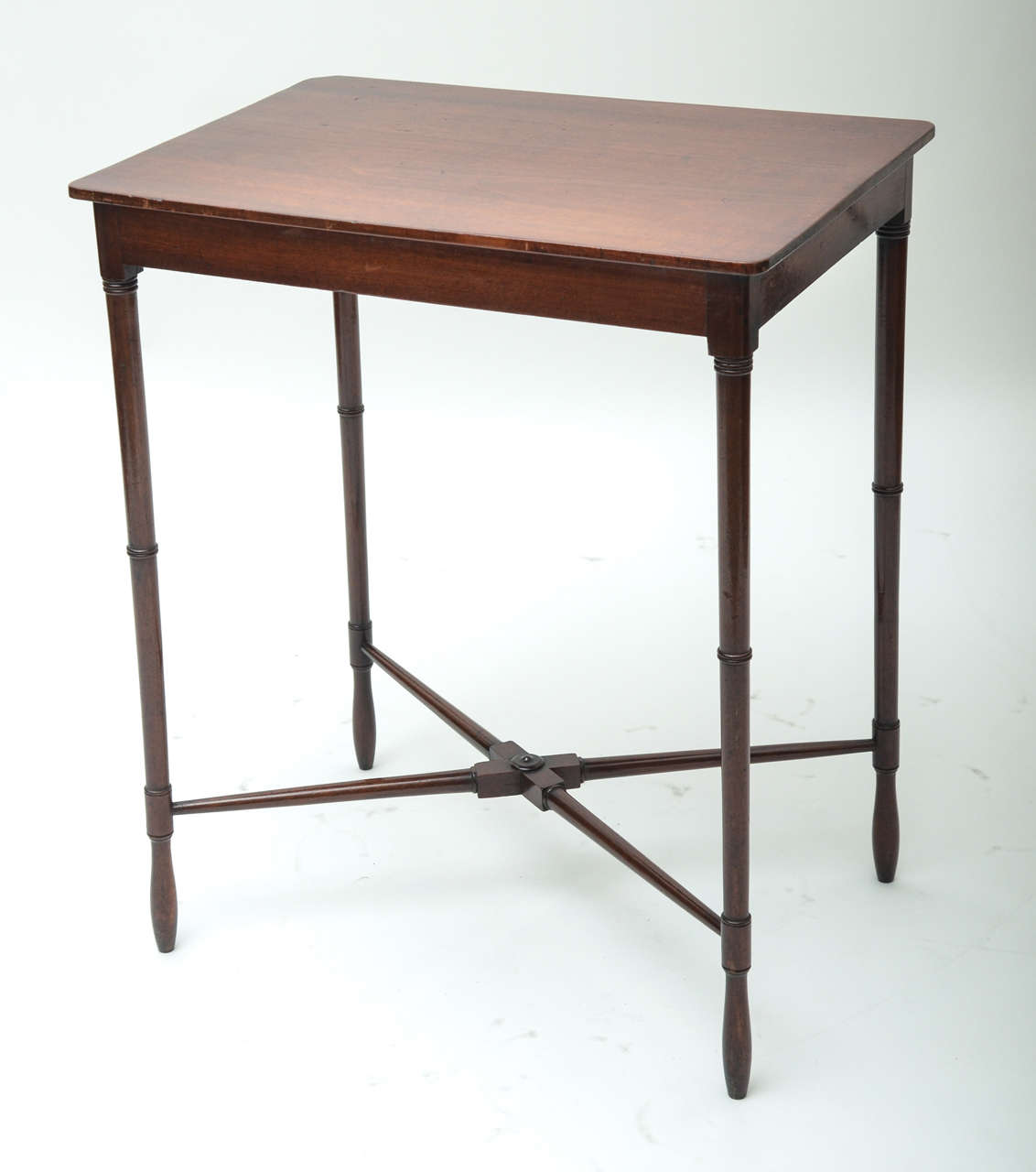 A period table with cross-stretcher and ring-turned legs.