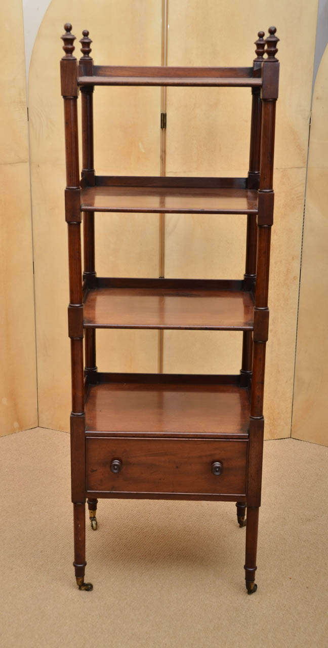 Early 19th century étagère with four tiers, one with a drawer, turned urn finials and supports, original wooden knobs.