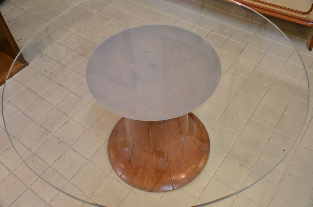 A round glass top and satin wood base.