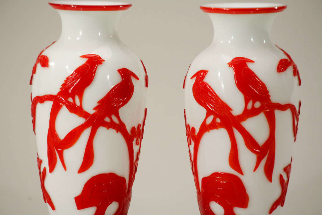 This striking pair of Chinese Peking Glass vases have age and great quality. The vases are cased in a vibrant red and cut back to reveal the white ground color. This glass is made of two layers with the well-carved outer layer of birds, flowers and