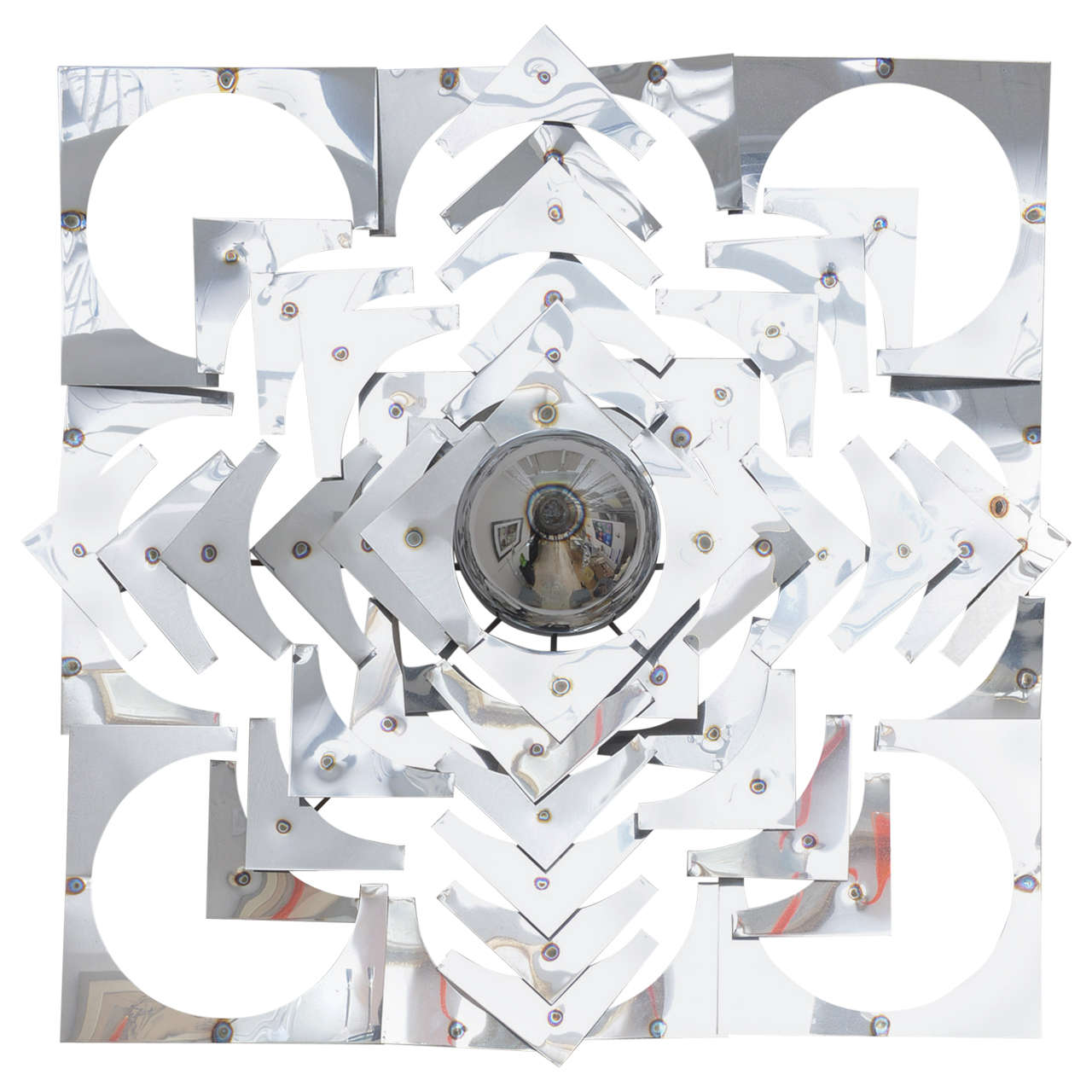 This large-scale wall sculpture was created in the 1970s and is very much a take on the kaleidoscope with its geometric shapes and forms in a stylized pattern.  The use of polished chrome gives the piece great deal of movement as the light plays