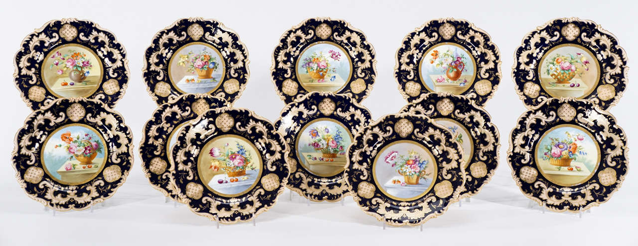 A decorative and beautifully hand-painted set of 12 Cauldon dessert plates with shaped rims trimmed in gold with central floral decoration. Each plate depicts a unique flower arrangement, framed with a cobalt blue border, set asymmetrically in the