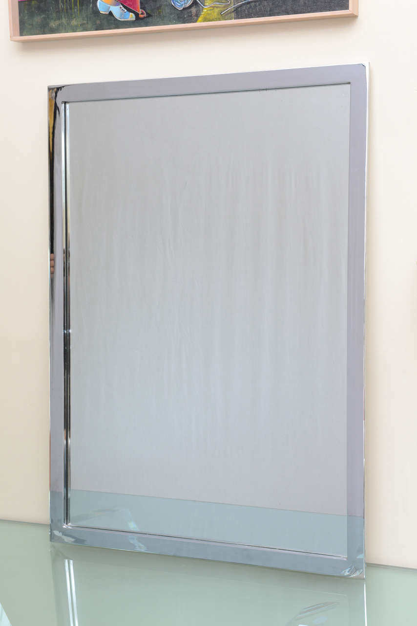Stunning Mid-Century Modern rectangular wall mirror in chromed steel.  Can be hung landscape or portrait style.  This mirror is a highlight in any room.