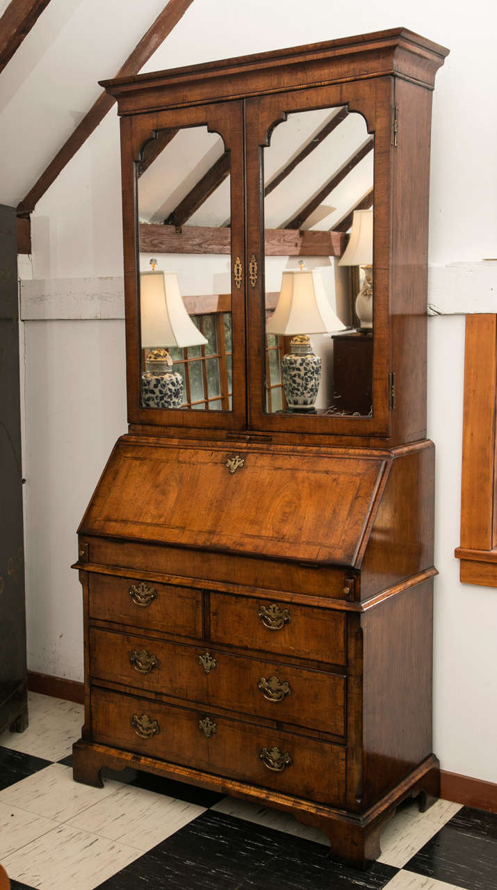 This Queen Anne style bureau bookcase / secretary with mirror doors was reproduced sometime in the latter half of the 19th century, but hews close to the original look and feel of a period original. The fully outfitted interior desk features a