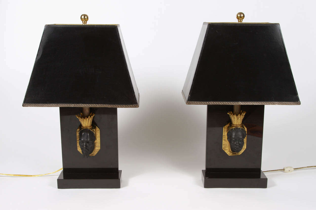 Pair of Hollywood Regency lamps, attributed to Maison Jansen.  Stone lamps feature high-releif busts with gilded tole frames and crowns that support the neck of the lamp, which is topped with spherical finials.  One lamp features a male bust, the