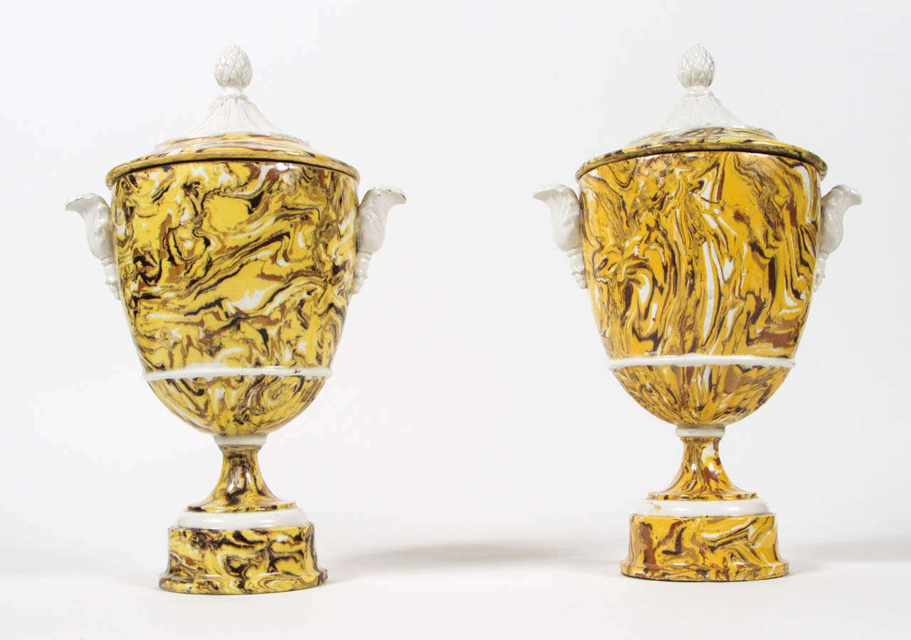 Two exquisitely marbleized pottery urns with contrasting faience accents.  Yellow ochre, mixed earth aptware in style of Provence, France. Details include pineapple finials, scroll handles and round pedestal base.  Late 19th century.  Made in Italy.