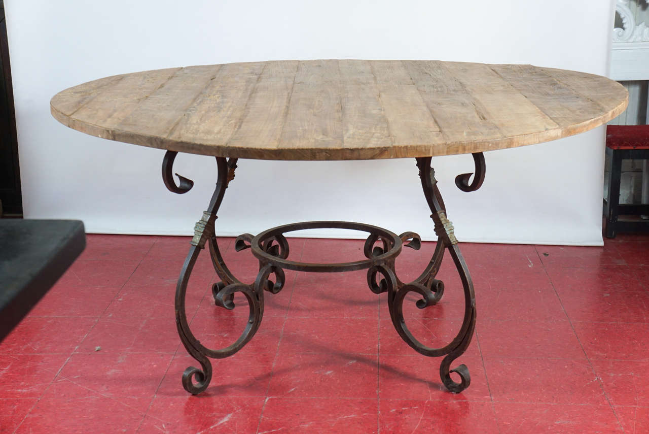 This rustic and elegant French Baroque style iron and teak wood round table can be used indoor or outdoors. The top made with reclaimed teak wood, thick scrolled hand forged iron base with a rust finish and some gilt. Excellent condition. A perfect