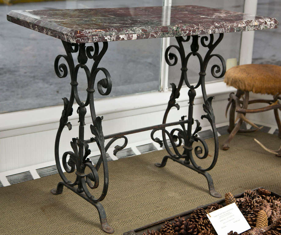 A pair of wrought iron console tables, each having marble tops supported on scrolling and foliate decorated bases.