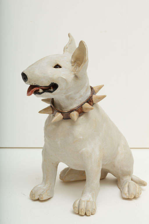 A superbly sculpted piece capturing the Bull Terrier's personality. He wears a large studded collar around his neck. His collar and paws are hallmarked with an