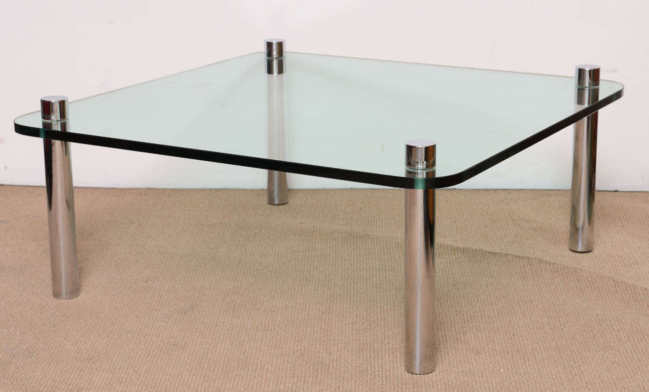 Stunning high quality minimalist chrome and thick glass cocktail table is in perfect condition. The glass has been replaced. The heavy tubular legs pierce the glass. The table is also very sturdy. A perfect addition to any design from Modernist to