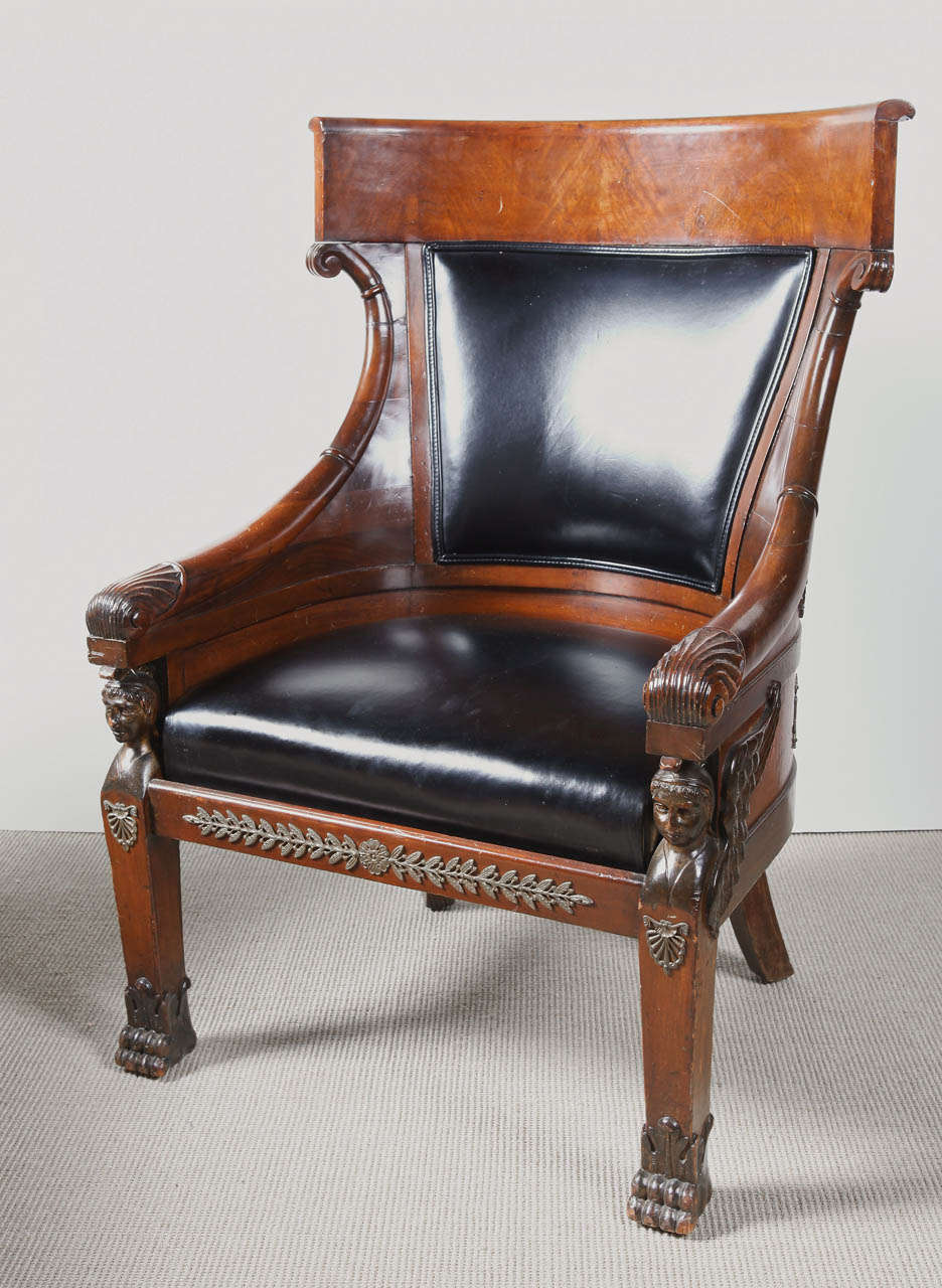 Empire mahogany bronze-mounted, black leather upholstered armchair; carved crestrail, downswept arms w/shell-carved terminals, supported by carved, winged female cartyatids, traces of gilding.  Squared legs ending in paw feet. C. 1810-1830.