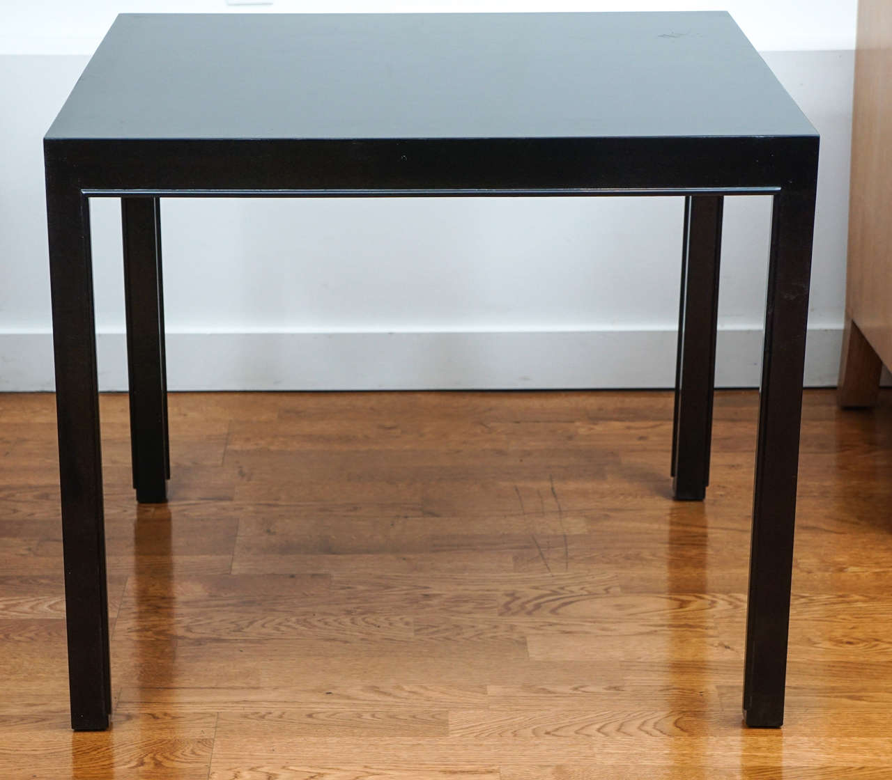 With its sleek, simple lines, this midcentury side table, by Dunbar, is extremely handsome. Newly lacquered, bearing its original metal label.