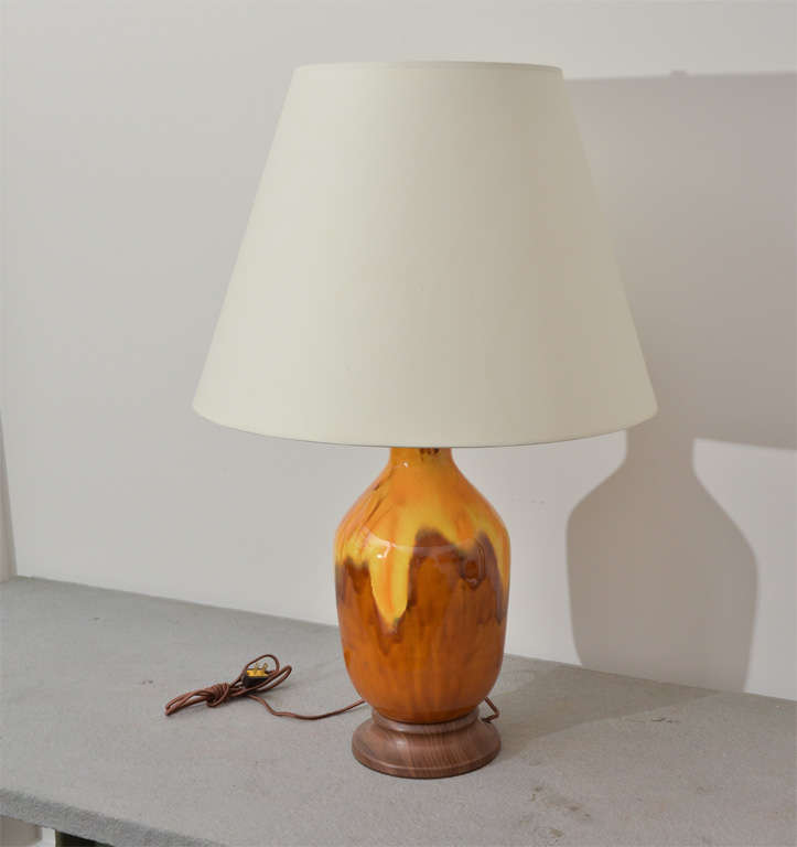 Brown and yellow ceramic vase converted into a lamp with wooden base and brass fittings. Brown silk cord. Shade is not included.