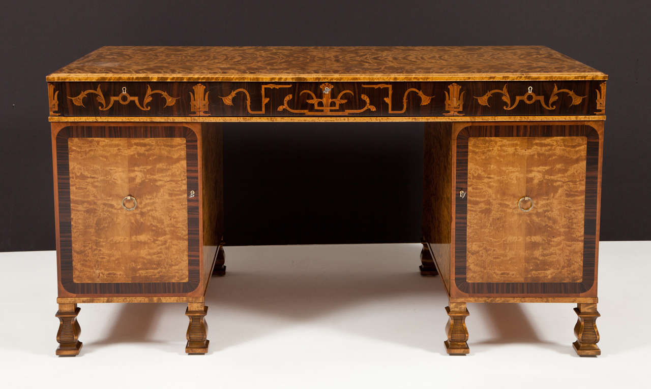 A Swedish Grace period flamed birch and rosewood pedestal desk with fruitwood inlays, designed by the renowned architect and furniture designer: Carl Malmsten (1888-1972) Produced by A.B Svenska Mobelfabrikerna - Bodafors, Circa 1930-1940. In three