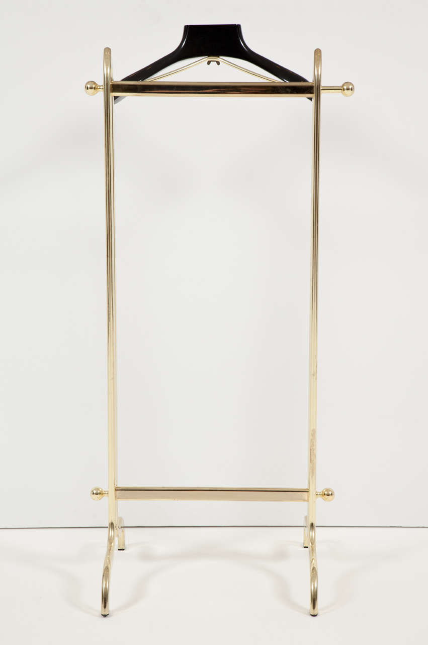 Elegant and refined Mid-Century Modern brass-plated men's valet with black lacquered coat hanger. Sturdy, solid and heavy, this valet is in excellent condition. This vintage piece is on display on the 1stdibs showroom at the New York design center