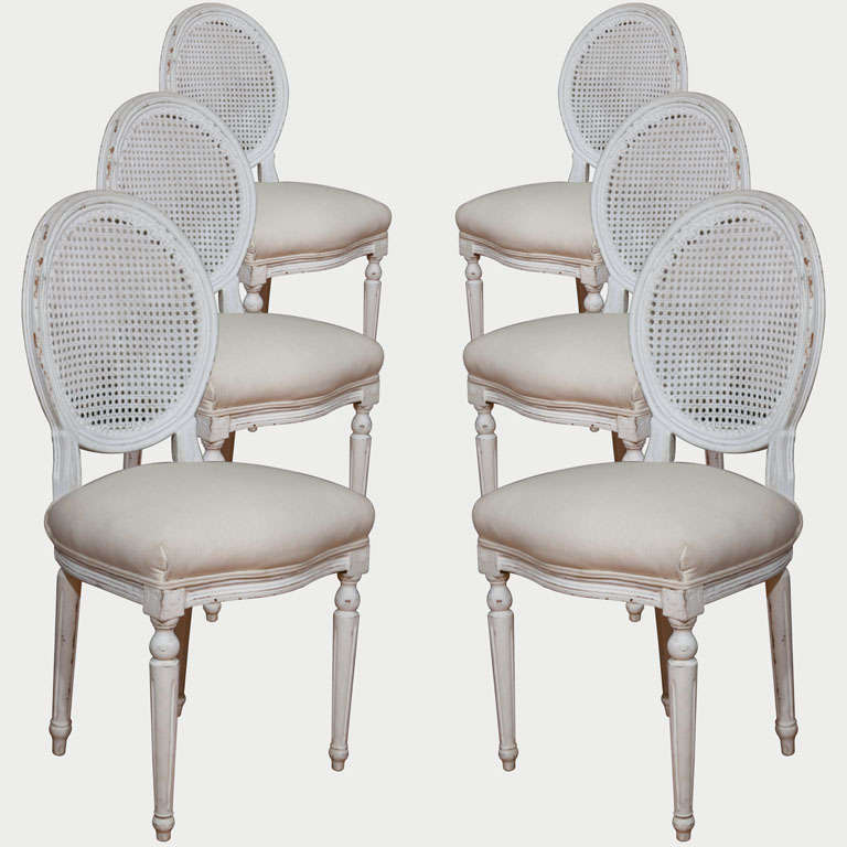 These white oval cane back chairs with their generously crowned seats will keep you comfortable for hours of dining. Fluted, straight legs preserve a clean, uncomplicated line that blends with almost any table. The classic formality of these chairs