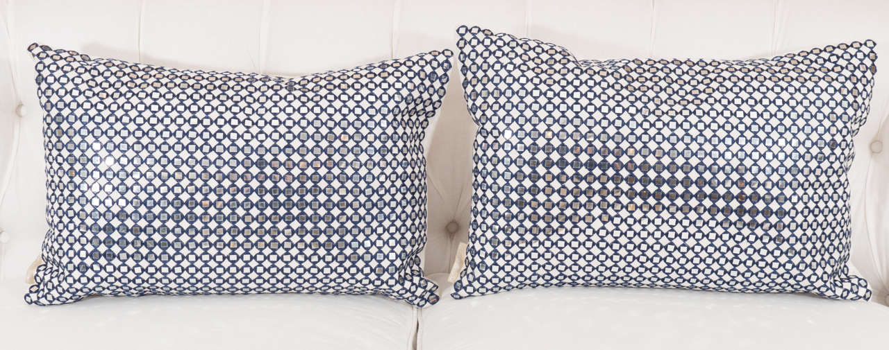 A pair of pillows with sequins surrounded by a dark navy stitching, backed in a cream chenille and very chic!