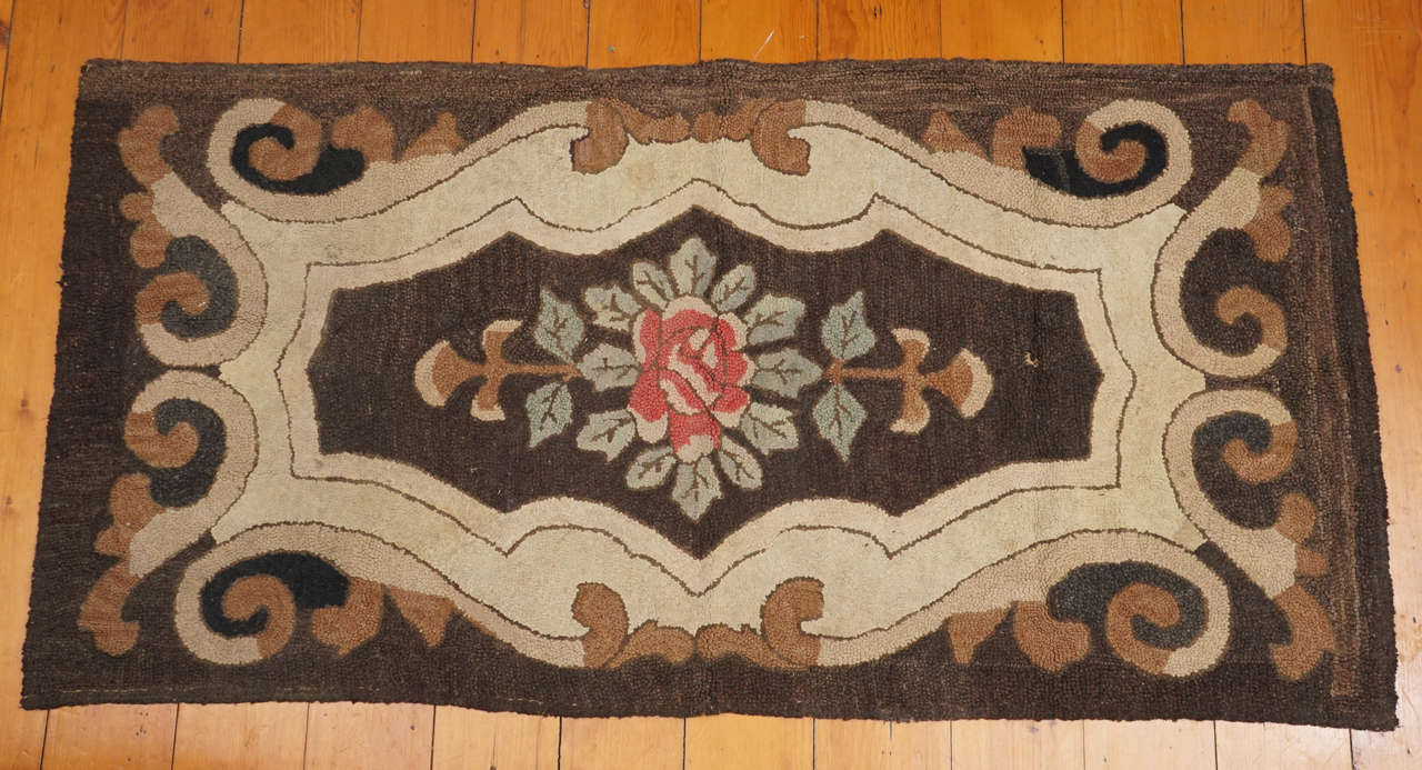 Rectangular American wool hooked rug with floral decoration in the center. Hand stitched burlap backing, late 19th century. Some wear but in overall good condition.
