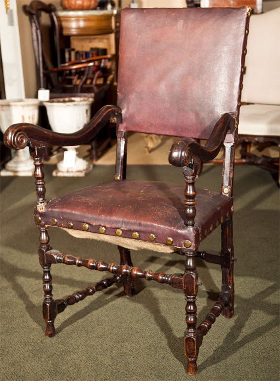 A 17th century Continental walnut armchair with turned legs and stretchers upholstered in brown leather.  Possibly Spanish.