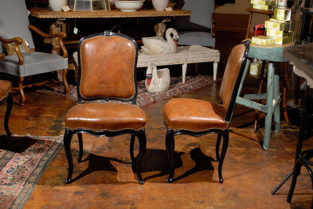 Set of 8 French leather and ebonized chairs.<br /> <br /> To see more items from Foxglove Antiques, please visit our website: www.foxgloveantiques.com