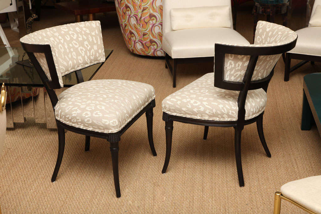 These elegant Grosfeld House Hollywood Regency side or slipper chairs have an unusual beaded wood detail, that is pierced carvings to the apron of the front of the chairs. The saber splayed legs add a sheer elegance. They have been re-upholstered in