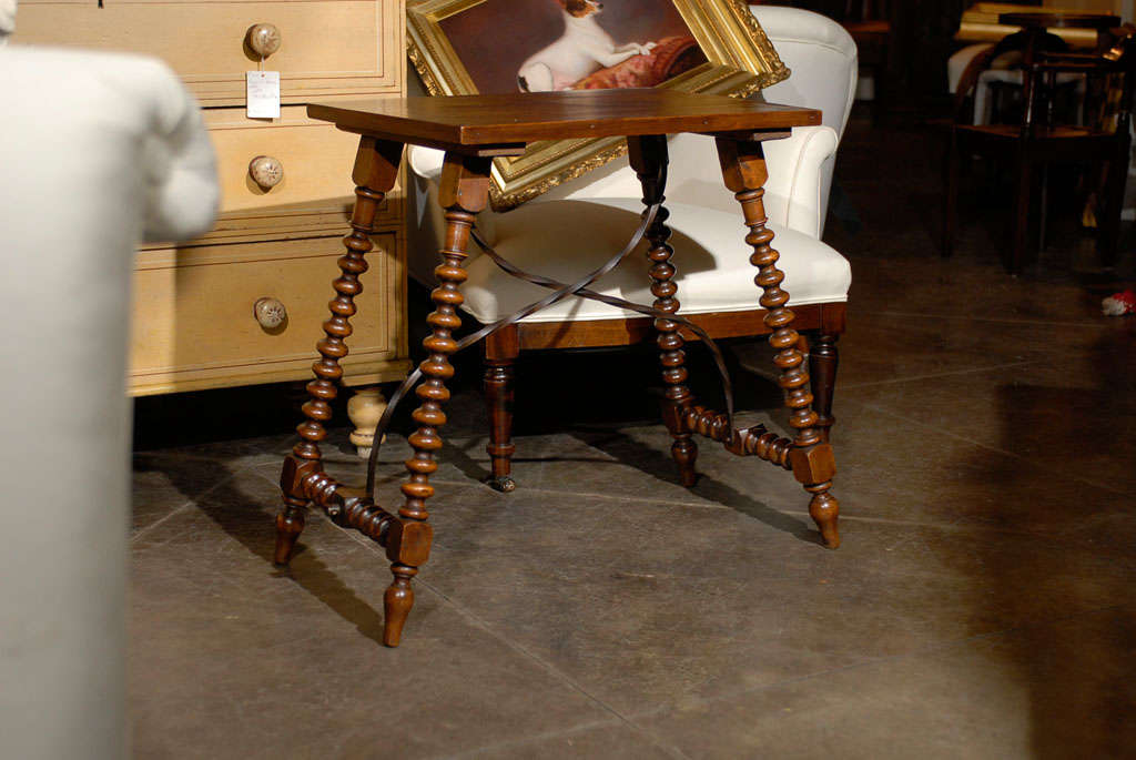 This petite Spanish wooden side table from the turn of the century features a rectangular top with delicate veneer, alternating lighter and darker finish. The table is raised on four splayed bobbin legs connected to one another with side stretchers,
