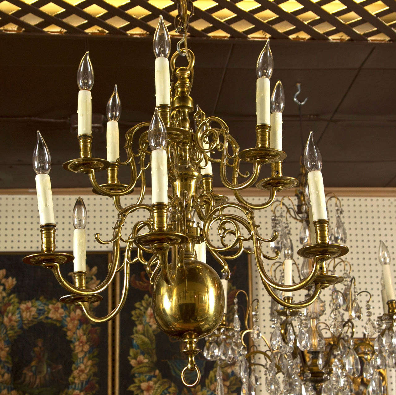 a  2 tier  12  light,   brass chandelier in the Dutch colonial  style.  scrolling arms emanate from central fittings. ring lower and  upper finial.