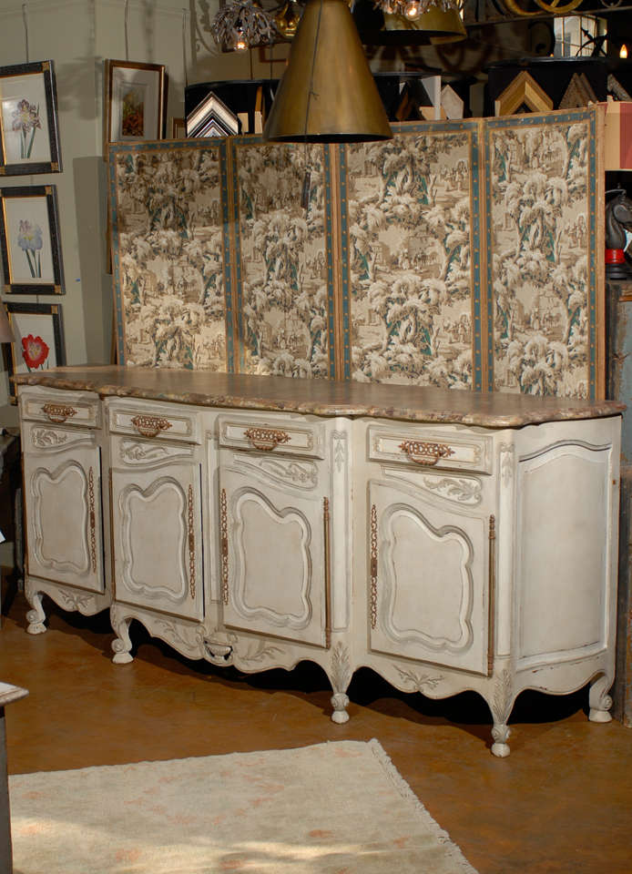 19th century French Provincial paint decorated faux marble top enfidale, the shaped top surmounting an offwhite double door cabinet flanked on either side by a single cabinet all opening to storage and raised on scrolling squat feet.