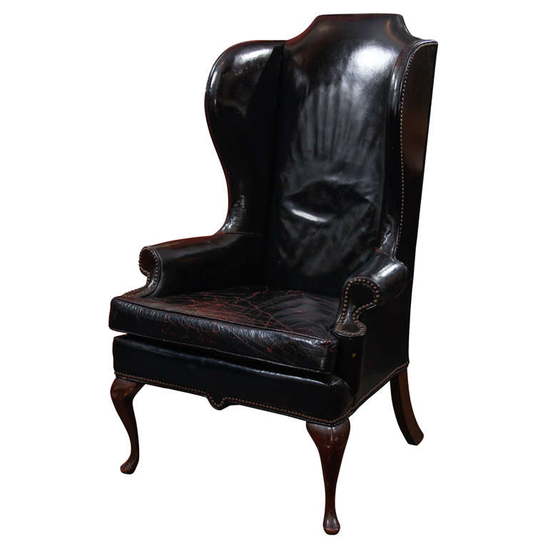 black leather wingback chair with touches of red in seat