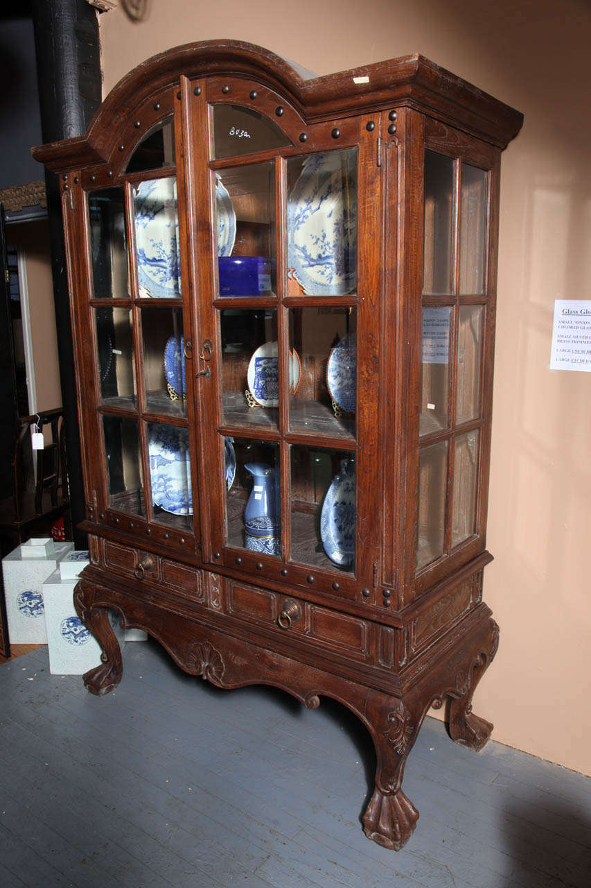 A large vintage Rococo style hutch from Java with bonnet top, double glass doors and sides. Born in Java during the 20th century, this large cabinet features an exquisite bonnet top, sitting above a pair of double doors with paneled glass and studs