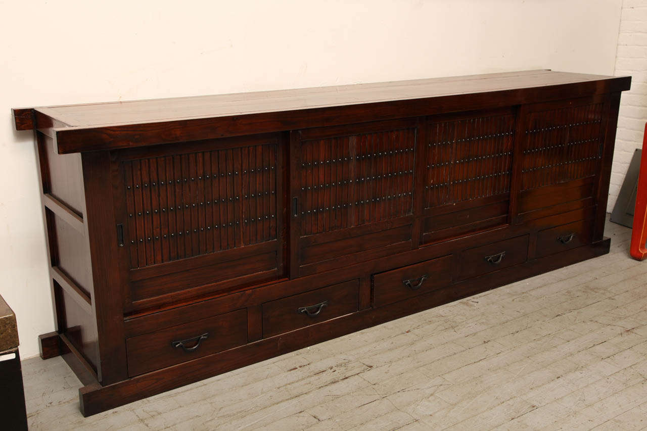 A long elmwood Mizuya Dansu Japanese style long buffet with sliding doors over five drawers. This Mizuya Dansu, a typical Japanese kitchen chest, was made in China during the 20th century from elmwood in a Japanese style. This Mizuya Dansu buffet