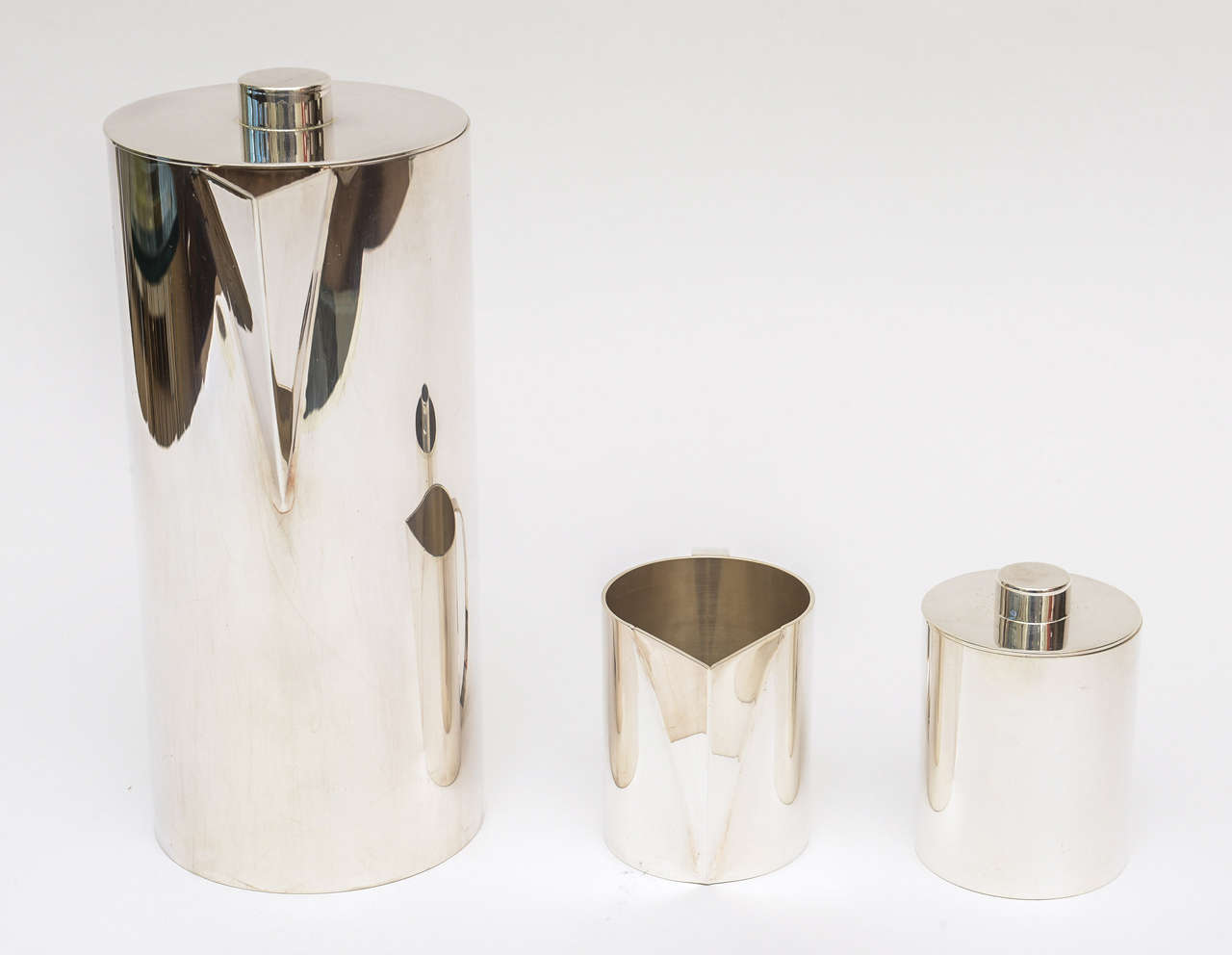 This modernist silver plate coffee service by Swid Powell for Calvin Klein is timeless. It has been all polished. Signed on the bottom. It is from the 1980s. It has a coffee pot and the cream and sugar vessels. Timeless. There is not tray but we do