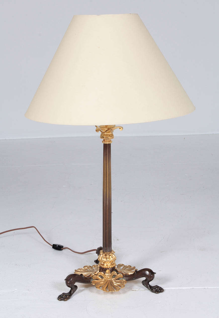 Danish table lamp designed by the architect Michael Gottlieb Bindesbøll (br.1800 died 1856)  Mid 19th Century, fire gilded bronze and patinated bronze, with a reeded stem raised a on tripod base with anthemion leaves and animal paws. Converted from