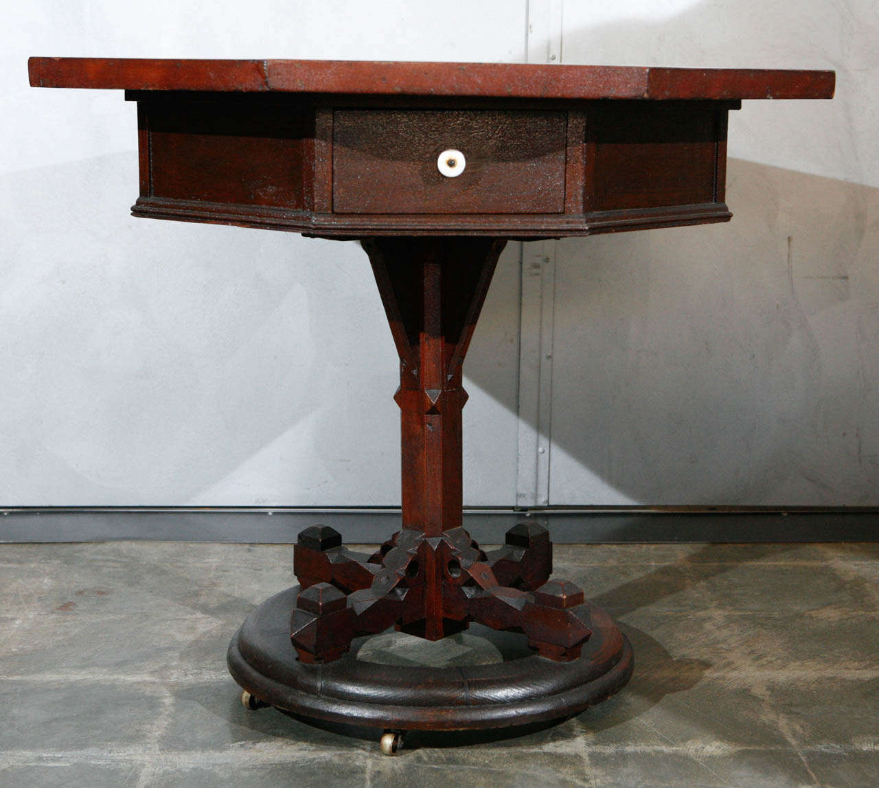 A most unusual and interesting American, 19th century, table having an octagonal top, recessed skirt with two drawers, on a central column which stands on a circular base with wheels. The top has a mysterious and intriguing panel veneered in exotic