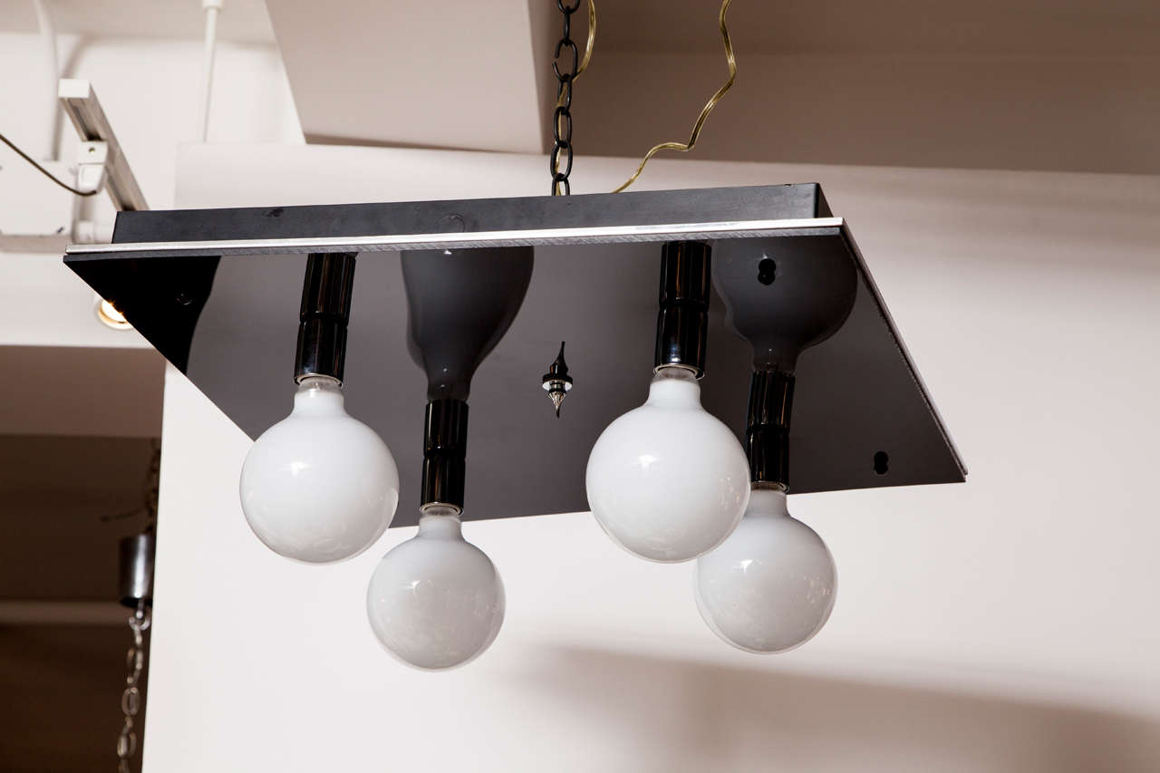 A modernist flush-mount light fixture crafted from black glass and chrome.  USA, circa 1970.  Features a black glass panel accented with chrome; four standard sockets hold oversize globe bulbs; 100 watts each max.