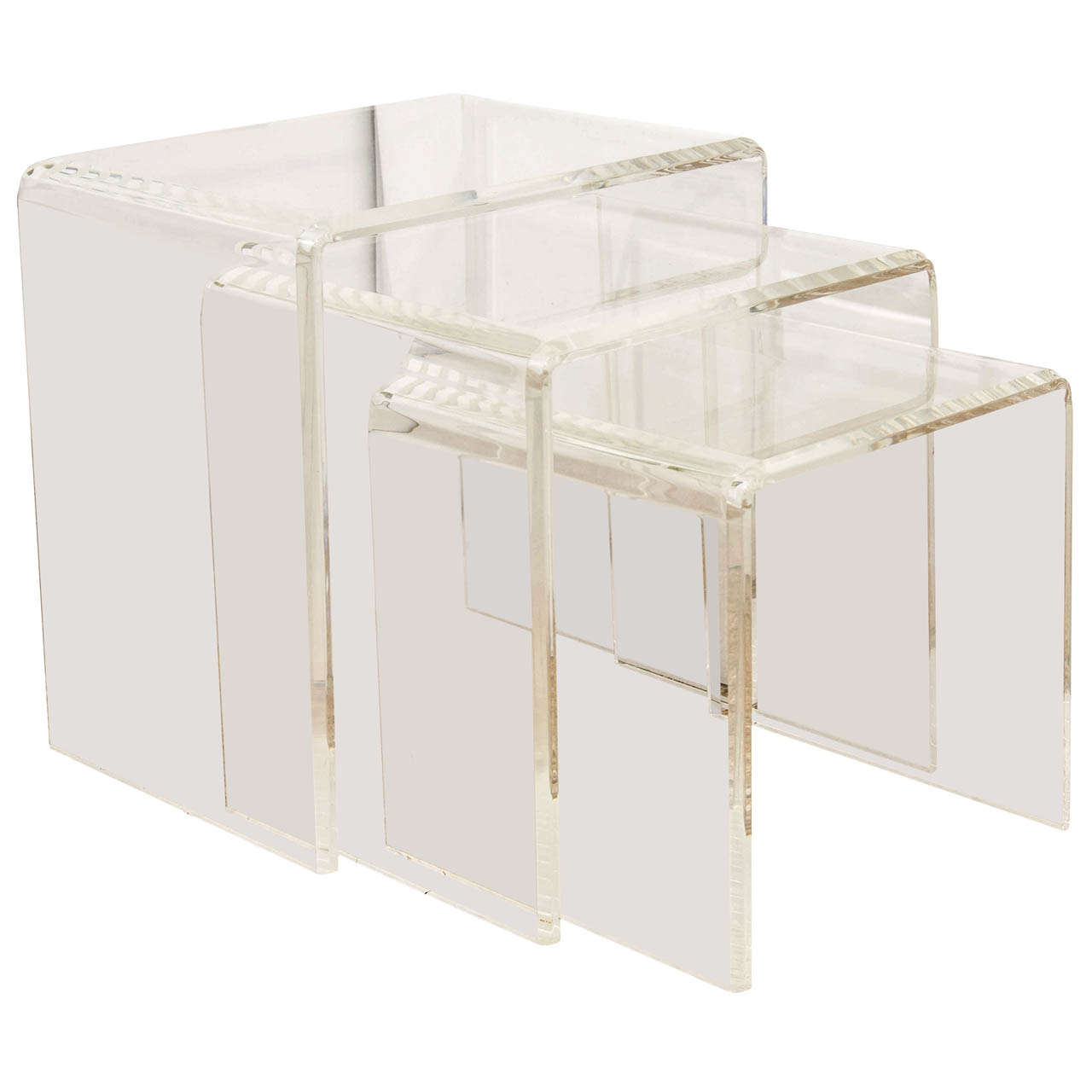 A set of three lucite nesting tables