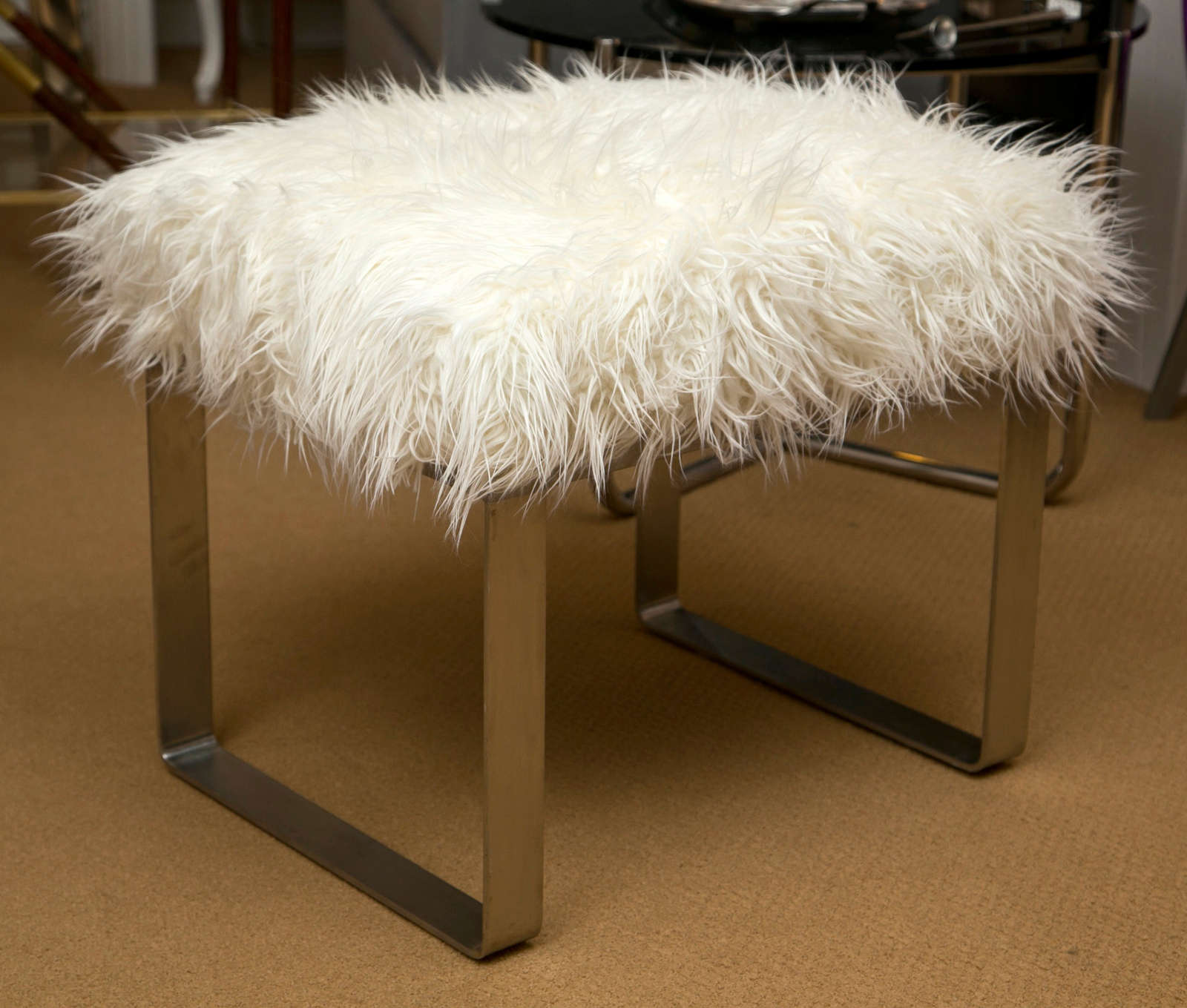 Newly upholstered in white faux Mongolian lamb. Heavy brushed steel base. Great as a bench, vanity stool or tuck under a console.