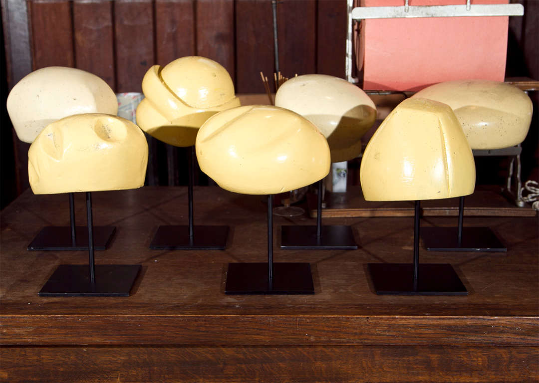 Seven different style wooden hat forms from the 1930s. Each is displayed on a metal stand.