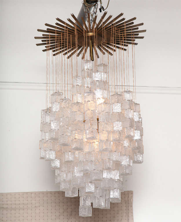 EXCITING LARGE CHANDELIER MADE IN VENICE 1960'S BY MAZZEGA, THE BLOWN GLASS DROPS ARE DONE IN A REGATO TECHNIC TO RESEMBLE ICE HANGING FROM CHAIN FIXED TO A WONDERFUL BRASS CANAPE.